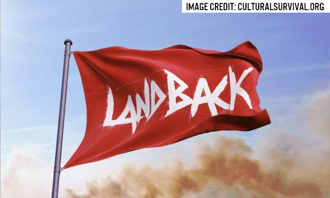 The Red Land Back flag flies in a smokey blue sky